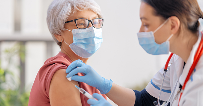 A woman in a face mask administers a vaccine shot to an elderly woman in a face mask